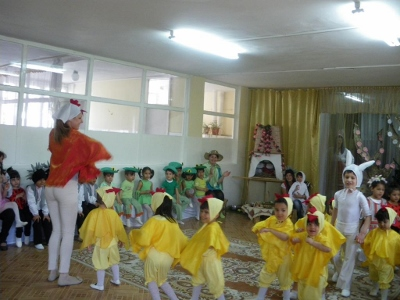 Children in yellow and green, standing in a circle with an adult in white and red