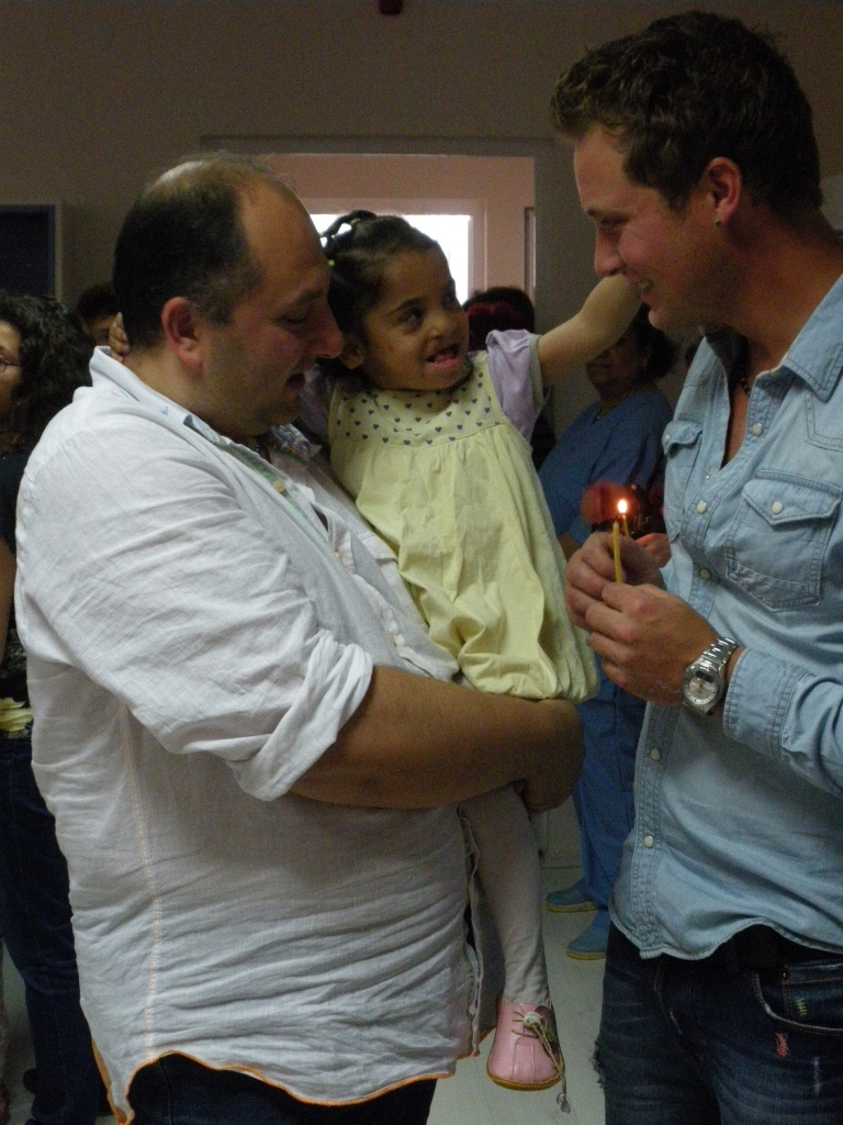 Man in white shirt holding a little girl in a yellow dress with pink shoes, looking at a man in a blue shirt