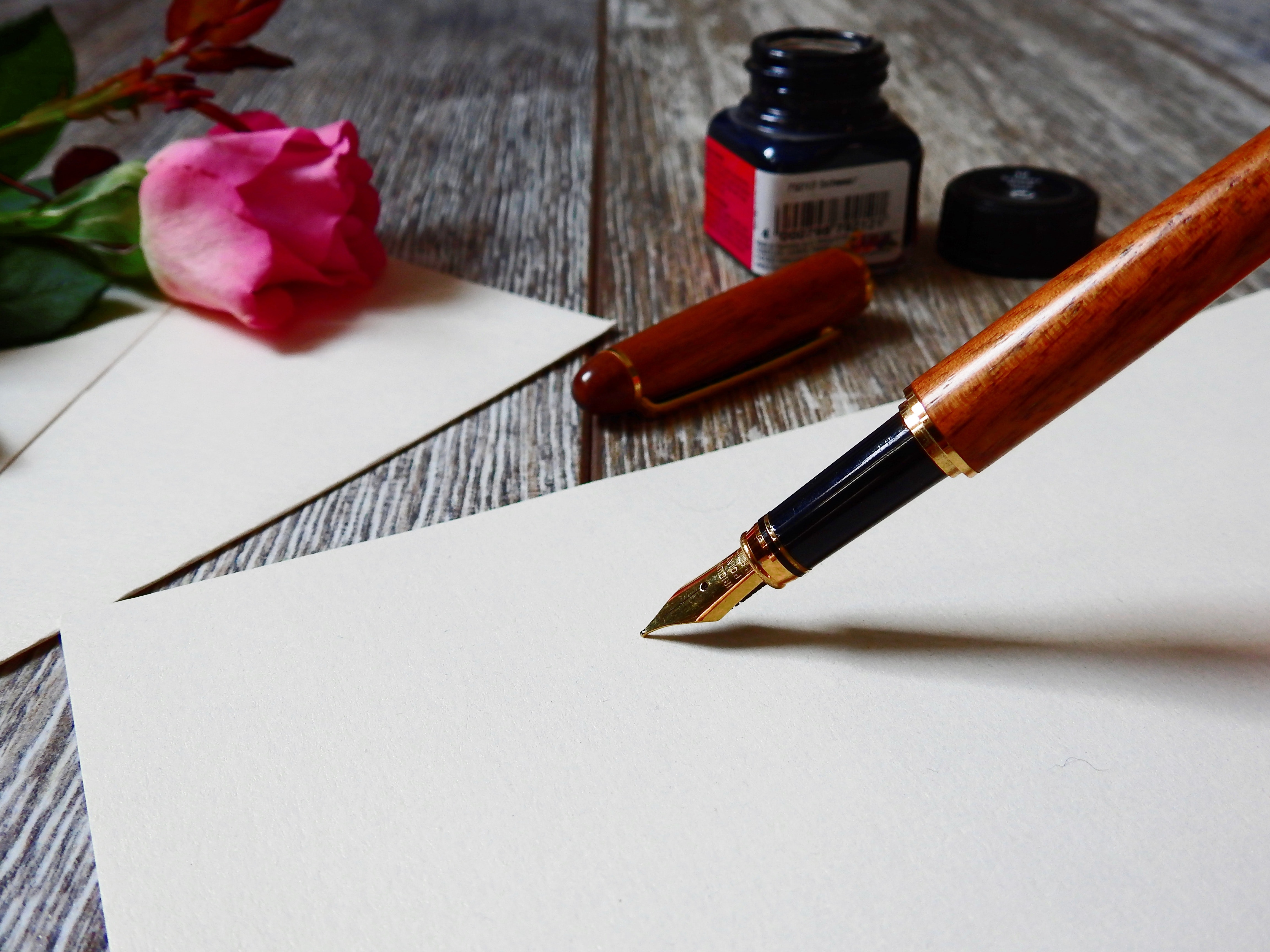 Wood fountain pen pressed against a blank piece of paper with cap, inkwell, and pink rose in the background