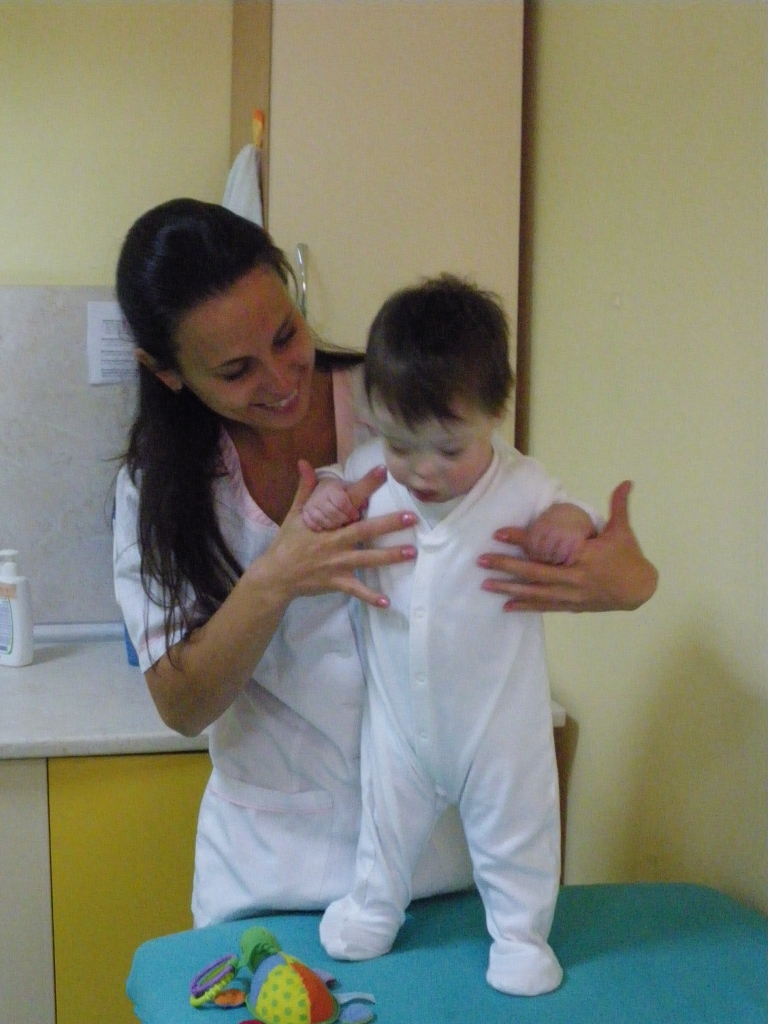 Petja, a physiotherapist, holding a child in a standing position